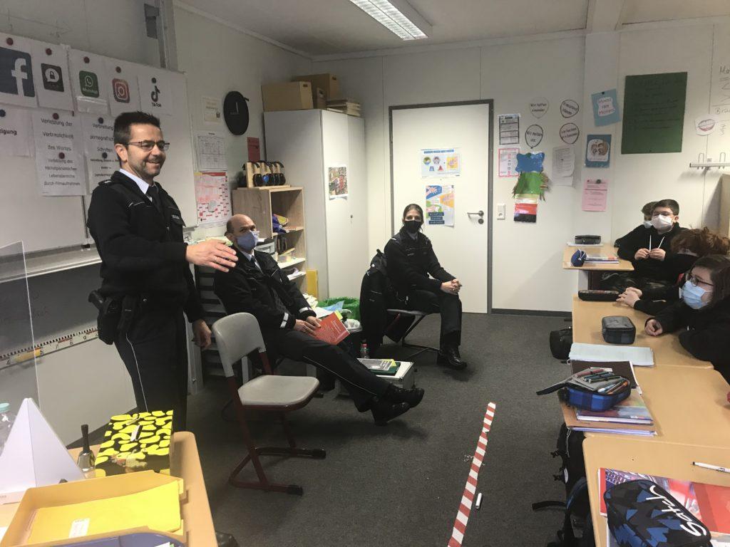 Bild mit Präventionsbeauftragtem der Polizei Wiesloch, Hr. Engelhardt, der in der Klasse den Vortrag hält