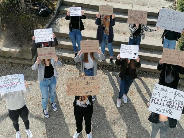 Mädchen der Klassen 10, die Schilder mit Forderungen hochhalten